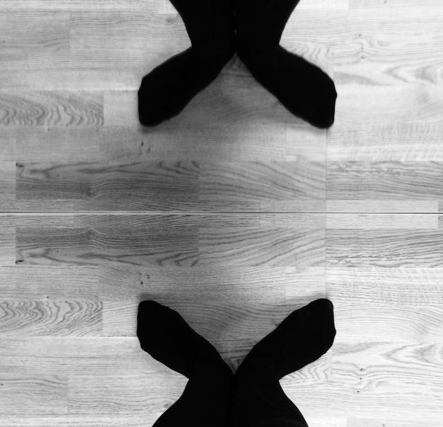 Svartvit bild. Ett par utåtvridna fötter som dubbleras i en spegel.
