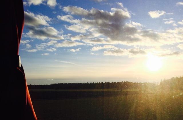 Solen på väg att gå ned utanför bussfönstret.