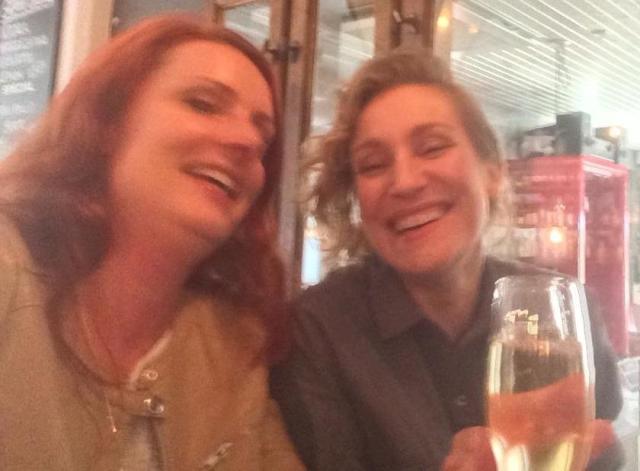Malin och Anita dricker champagne och skrattar.