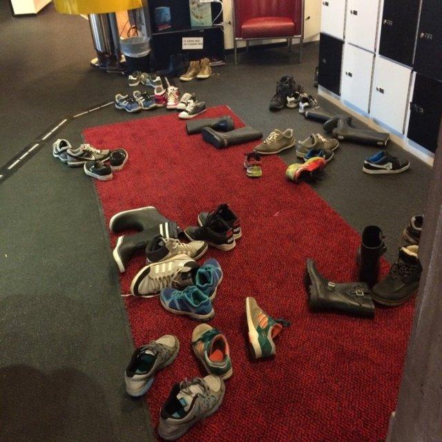 Barnskor som ligger slängda på en stor matta i hallen.