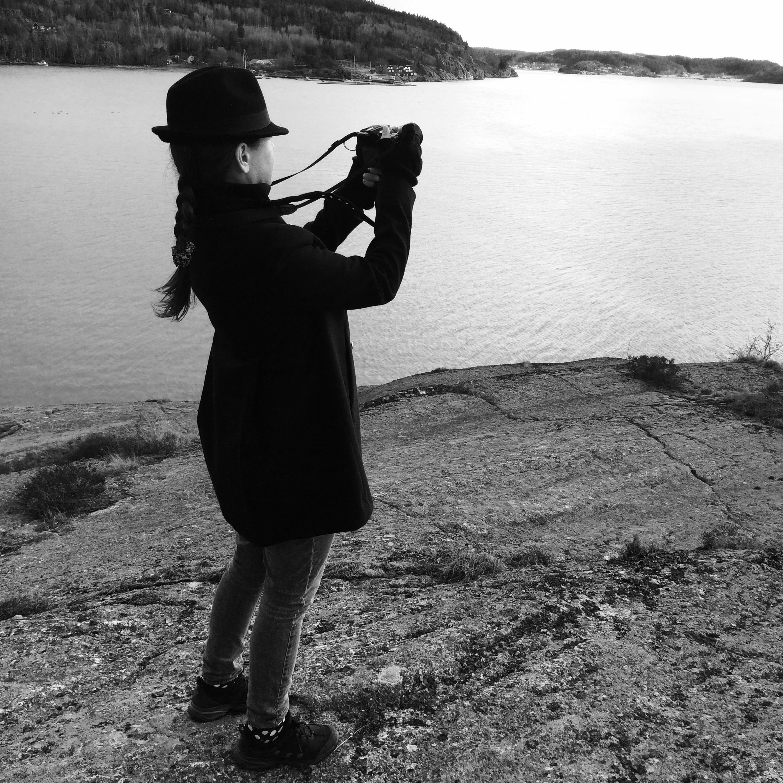 svartvit bild. kvinna med hatt, fläta och skepparkavaj syns bakifrån då hon fotograferar ut över havet.