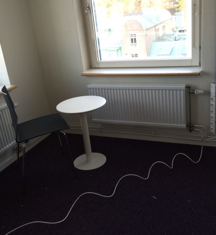 Rum med en stol och ett bord, en lila heltäckningsmatta och en krullig internetkabel dragen tvärs över golvet.
