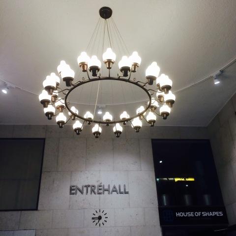 Rund lampkrona sprider ljus över en vägv där det står Entréhall. Intill finns en skylt där ddt står House pf Shapes. En klocka på väggen visar 06:45.
