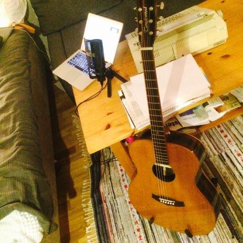 En gitarr står bredvid ett bord med en skrivmaskin, en dator, en mikrofon och en bunt med papper.