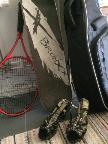 Ett tennisracket, en skateboard, en gitarr i ett gitarrfodral och ett par högklackade skor står på en hallmatta.