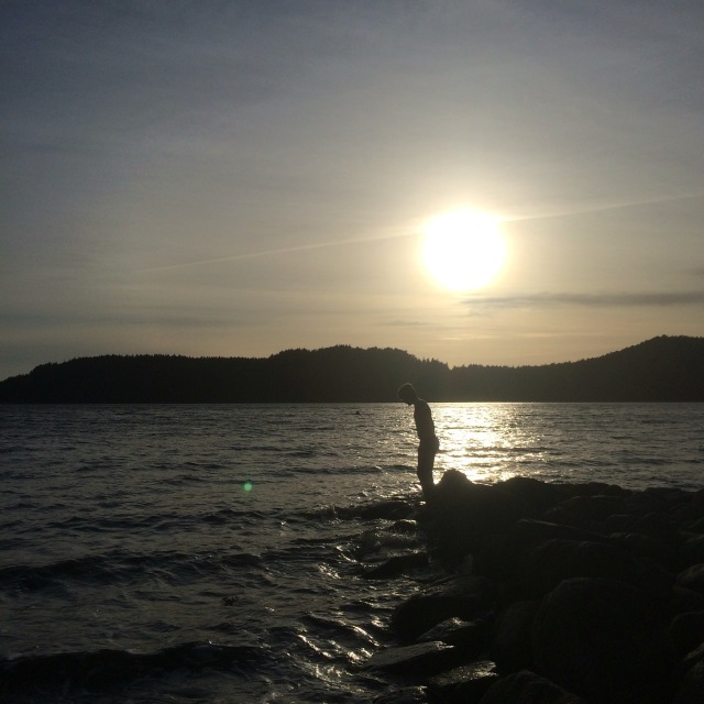 Silhuett av pojke vid vattnet i solnedgång.